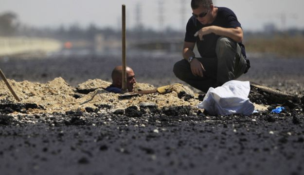 Israeli police sapper inspects the remains of a rocket fired by Palestinian militants from the Gaza