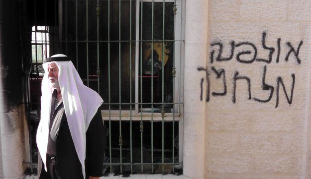 """A man outside the mosque in Jab'a on June 19, 2012. The graffiti reads """"Ulpana war."""""""