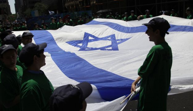 Children hold a large Israeli flag before the start of the Celebrate Israel parade in New York