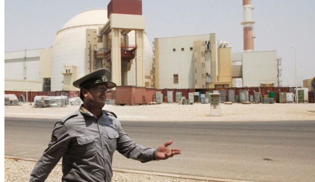 An Iranian security directs media at the Bushehr nuclear power plant.