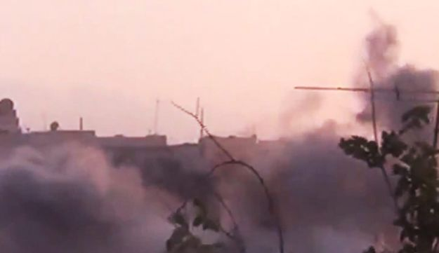Smoke rises from buildings following purported shelling in Homs, Syria