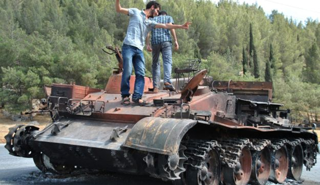 A Syrian man flashes the victory sign as he stands with his friend atop of a burned tank