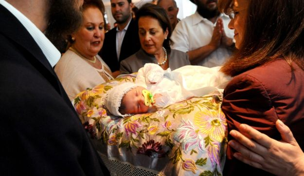 A Jewish baby rests on a pillow following his circumcision
