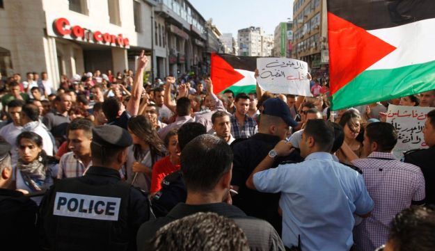 Palestinian protesters rally in front of  Abbas' security forces - Reuters - June 30, 2012
