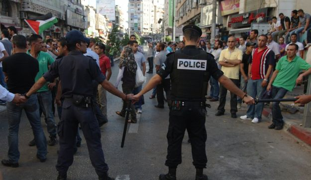 Palestinian police control the crowd in the West Bank city of Ramallah, on June 30, 2012