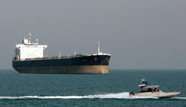 An Iranian Revolutionary Guard speedboat passes in front of an oil tanker on Monday, July 2, 2012.