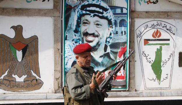 A PLO member in front of a portrait of the late Palestinian leader, Yasser Arafat, in Sidon, Lebanon