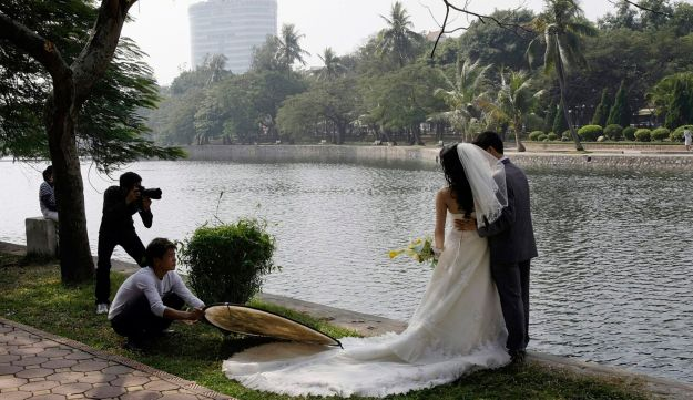 A couple pose for a wedding photo in a park.