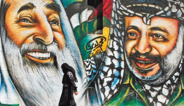 A woman walks past a mural depicting Sheikh Ahmed Yassin and Yasser Arafat in Gaza.