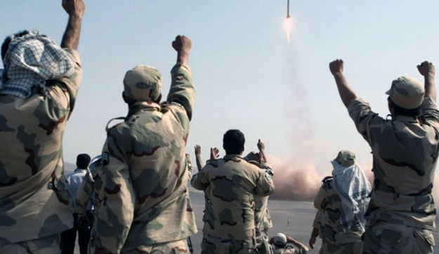 Iranian Revolutionary Guard members celebrate after launching a missile.