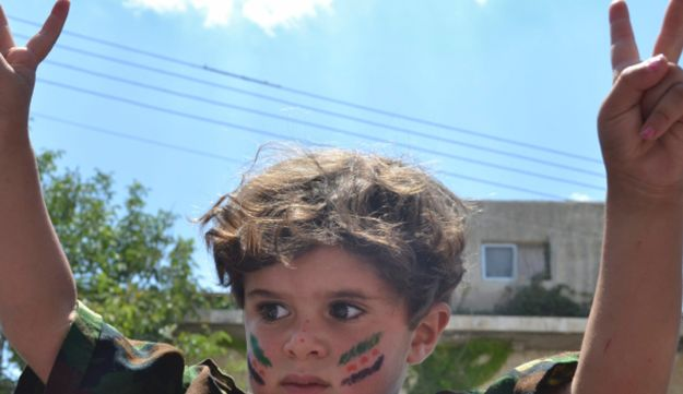 A child in a military uniform flashing the victory sign at an anti-Assad protest in Kafr Nabil