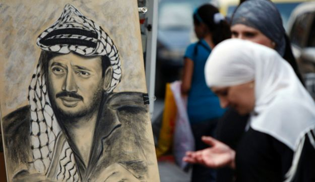A Palestinian woman stands by a drawing of late Palestinian leader Yasser Arafat.