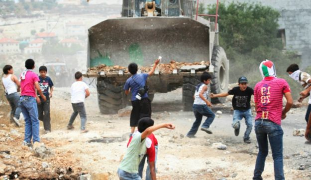 Palestinian youths throw stones at an Israeli military bulldozer during a protest