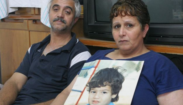 Eden Natan Zada's parents holding up his picture in 2005.