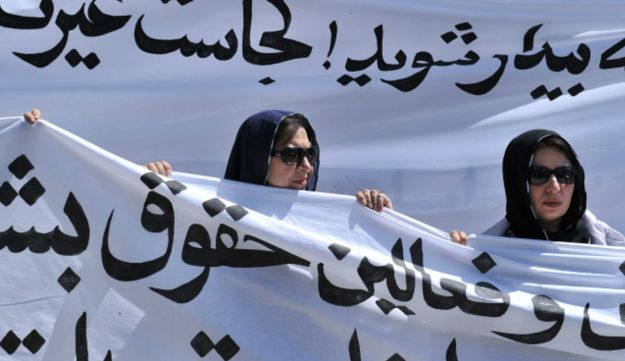 Afghan women march with banners to protest the recent execution of a young woman, July 11, 2012.