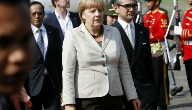 German Chancellor Angela Merkel walks with Indonesian Foreign Minister Marty Natalegawa