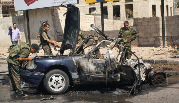 Syrian policemen inspect the site of a car bomb explosion on Mazzeh highway in the capital Damascus.