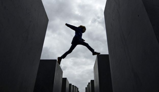 A visitor jumps from one pillar to another at the Holocaust memorial
