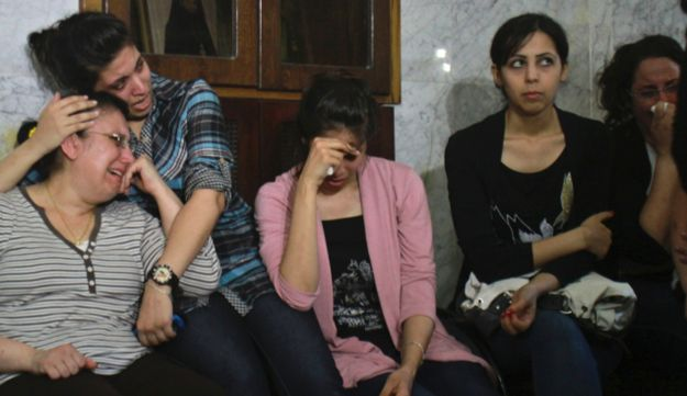 A Palestinian Christian Huda Al-Amash, right, and her her daughters cry during a rally.