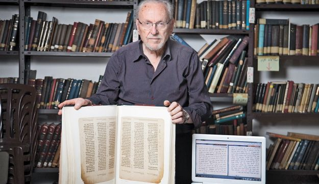 Prof. Menachem Cohen with his version of the Bible, both in print and in digital format.