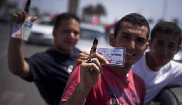 Libyan men hold their election ID cards while celebrating election day in Tripoli, Libya.