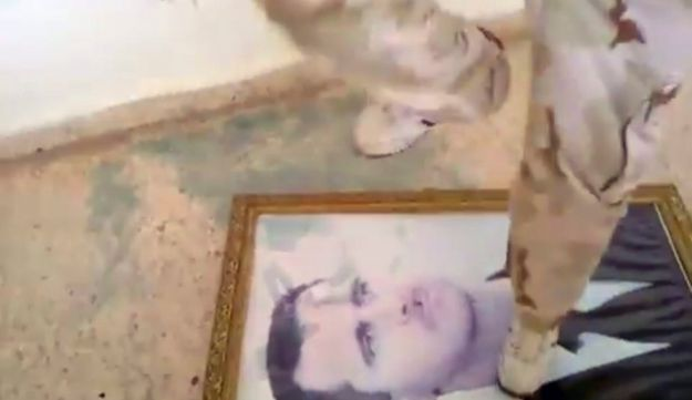 Protester stomping on picture of Assad