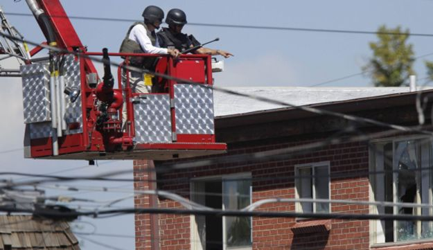 Law enforcement officers use a fire truck lift to inspect the apartment.
