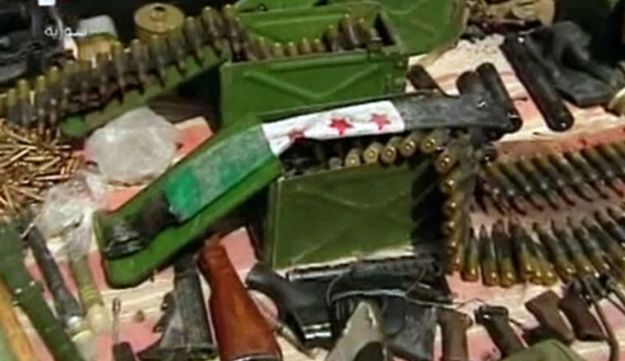 Syrian state television shows weapons, ammunition and a folded pre-Baath Syrian flag