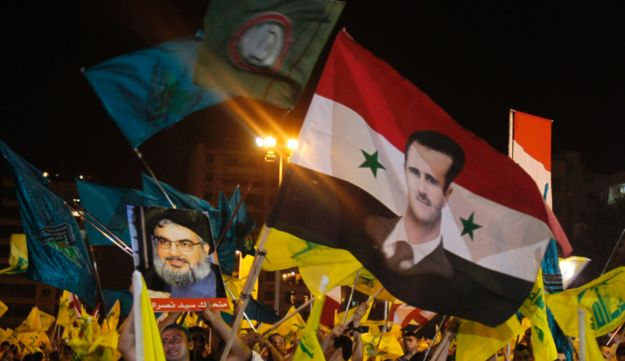 Supporters wave Hezbollah and Syrian regime flags.