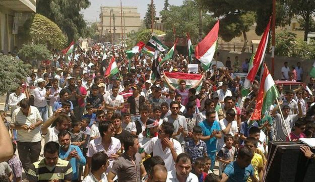 Demonstrators hold Kurdish and opposition flags during a protest against Assad - July 20, 2012.