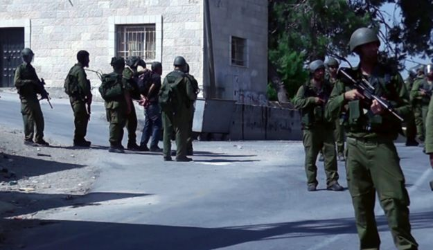Soldiers arrest a protester during a demonstration in the West Bank village of Nabi Saleh