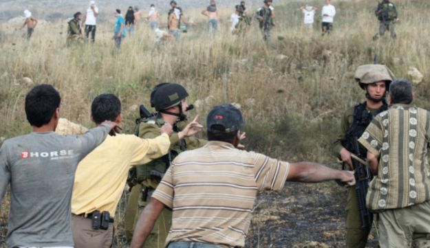 Palestinians talk to Israel soldiers during clashes between Palestinians and Jewish settlers