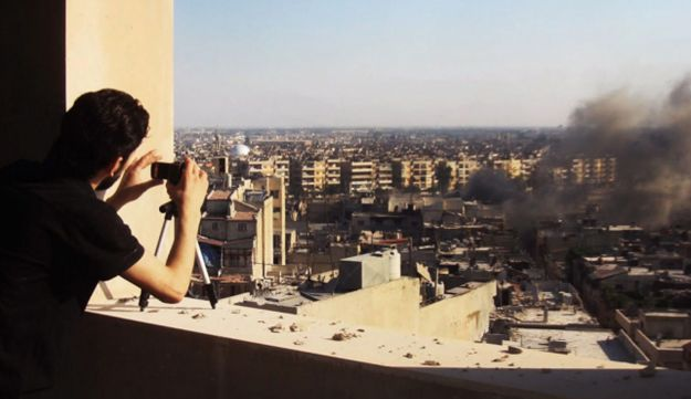 A Syrian citizen journalist documents Syrian forces shelling in Homs, Syria, on July 24, 2012.