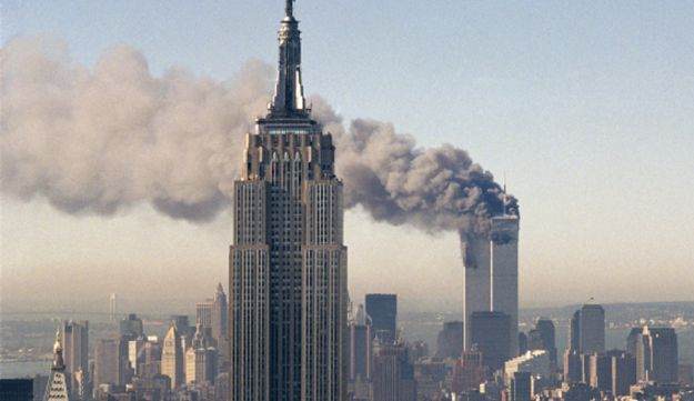 The twin towers of the World Trade Center burn behind the Empire State Building in New York, September 11, 2001.