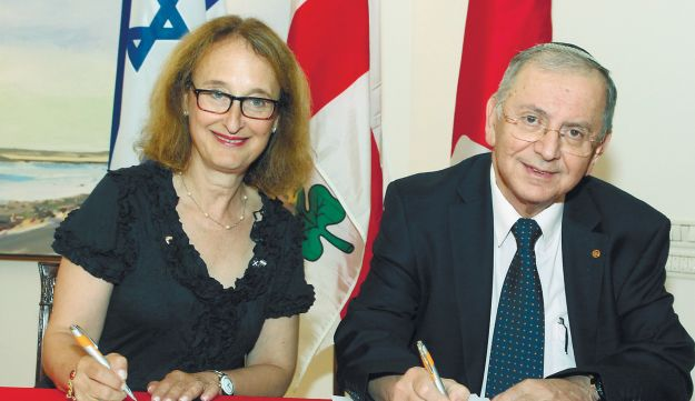 Goldstein, left, signing the memorandum with Kaveh.