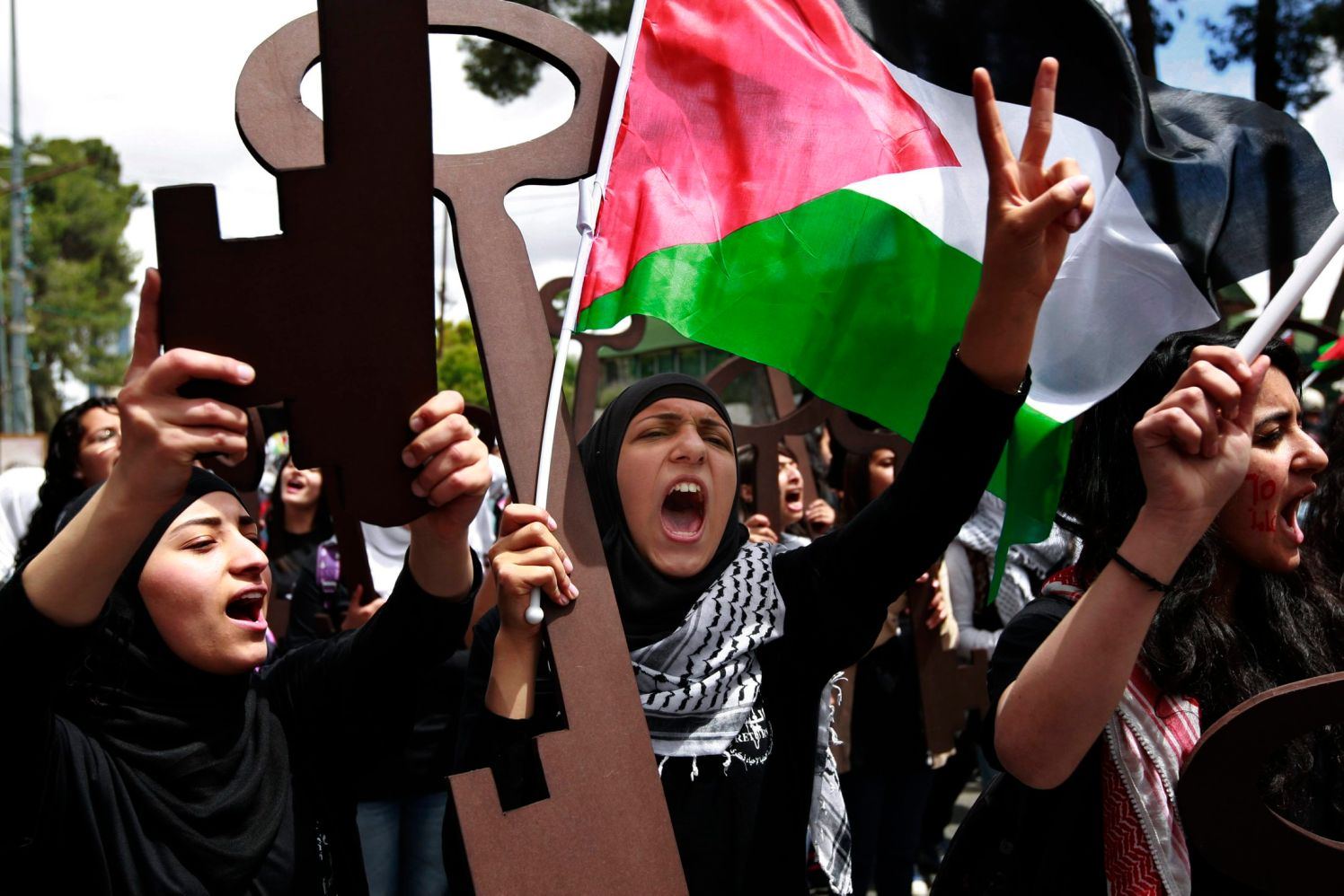 """Palestinian women hold symbolic keys and chant """"the right of return will not die,"""" during a rally to"""