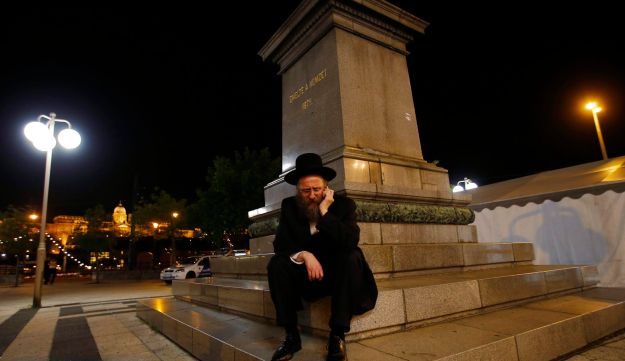 An Orthodox Jewish man sits outside the building where the 14th Plenary Assembly of the World Jewish