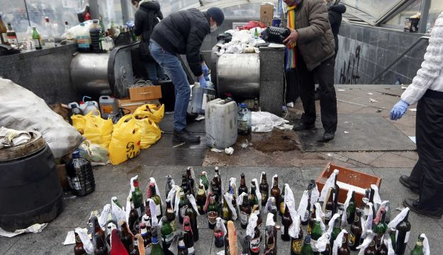Anti-government protesters prepare Molotov cocktails during clashes with riot police.