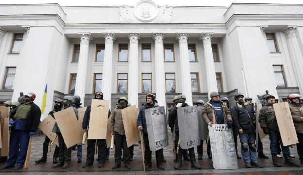 Anti-government protesters hold shields as they guard the Ukrainian Parliament building in Kiev