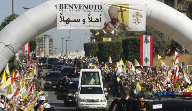 Crowd wave Lebanese and Vatican flags as they greet Pope Benedict XVI in his papamobile  in Beirut.