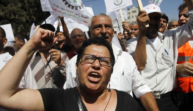 Palestinians hold placards during a protest against the rising cost of living in Ramallah.