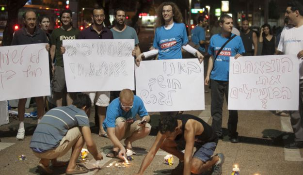 Activists carry posters, during a protest against ending daylight saving prior to Yom Kippur