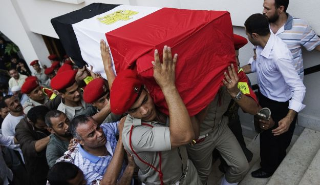 Egyptian military policemen carry the coffin of one of 16 soldiers killed