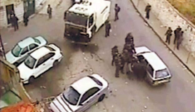 A frame grab from a security camera showing police officers arresting and beating a Palestinian man