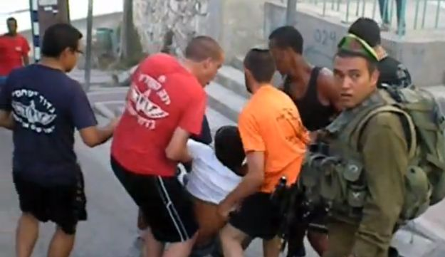 IDF soldiers in civilian clothes dragging a Palestinian man