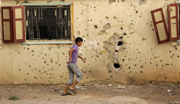 A Lebanese boy walks past a house that was hit by rockets during clashes in Tripoli.