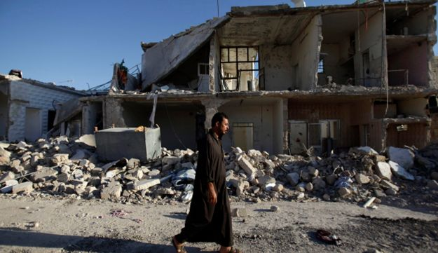 A Syrian man walks by a house destroyed in a Syrian government bombing last week