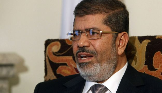 Egyptian President Mohammed Morsi talks during an interview with Reuters at the Presidential palace