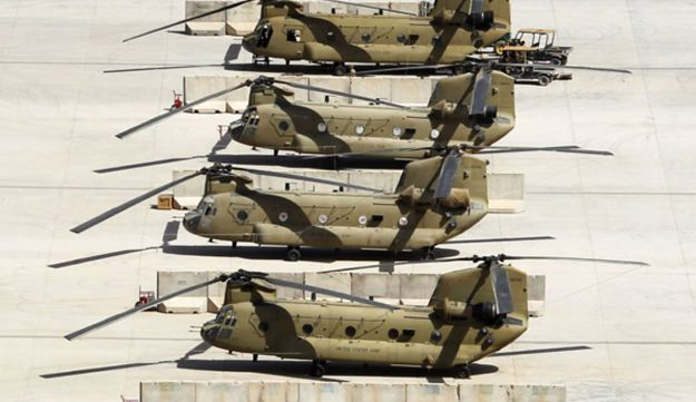 Four United States Army Chinook helicopters are parked on the tarmac at Kandahar Air Field in southe