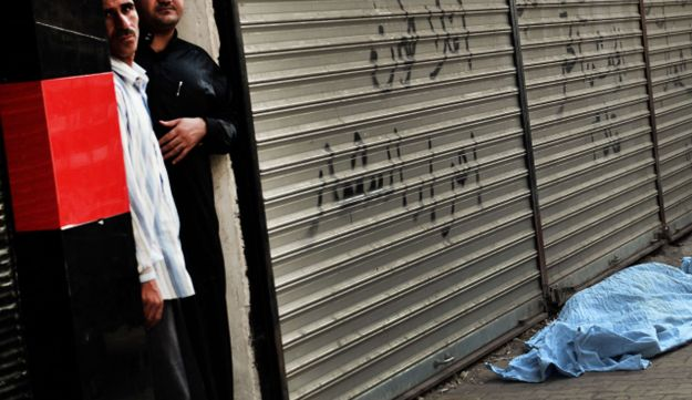 Syrians stand next to a body outside a hospital in Syria's northern city of Aleppo, on August 30, 20